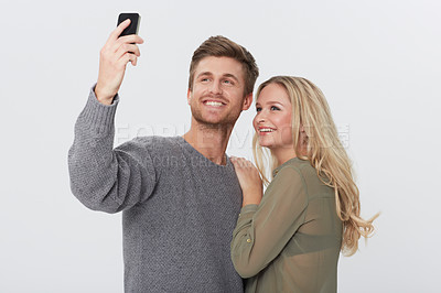 Buy stock photo Studio portrait of a happy young couple taking a self portrait with a camera phone
