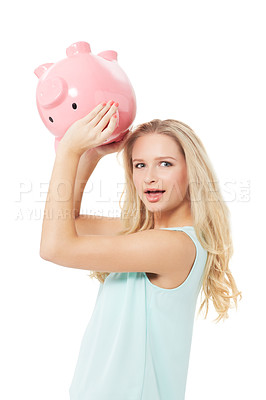 Buy stock photo A pretty young woman shaking her piggy bank and wondering where all the money's gone