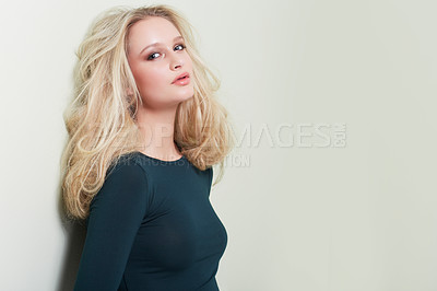 Buy stock photo A stunning young model leaning against the studio wall and looking at you confidently
