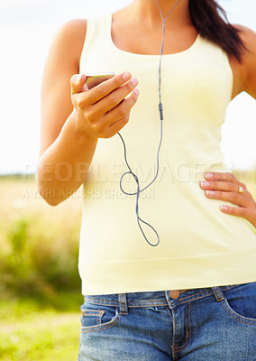 Buy stock photo Mid section image of a young female listening to an mp3, outdoors