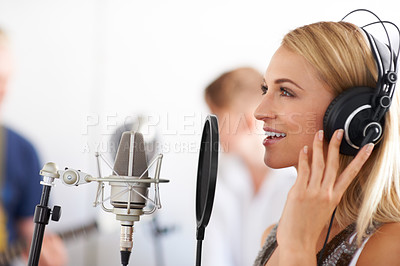 Buy stock photo Profile of a beautiful woman singing into a microphone with her two band members in the background - copyspace