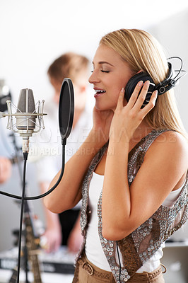 Buy stock photo Profile of a lovely young woman singing into a microphone with a band member in the background
