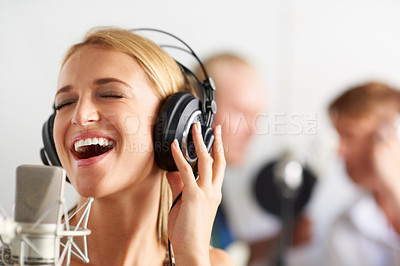 Buy stock photo A young blonde woman singing into a microphone with her band members in the background