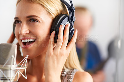 Buy stock photo A beautiful young blonde woman singing into a microphone with her band members in the background - closeup