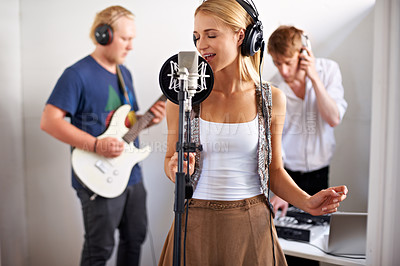 Buy stock photo A band consisting of three young adults busy recording a track