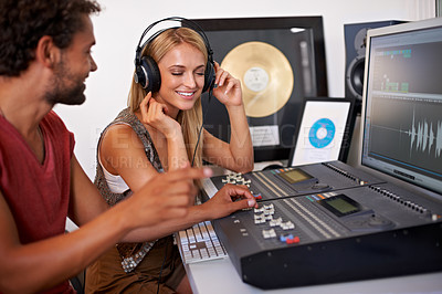 Buy stock photo Two happy young music producers working on a mixing desk with a gold album in the background
