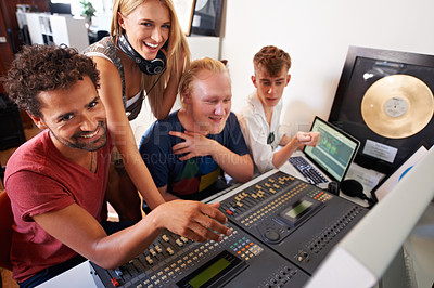 Buy stock photo Four young audio engineers working on a mixing desk