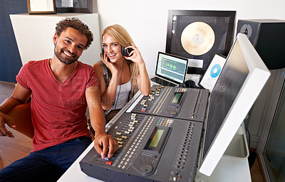 Buy stock photo Two young sound engineers sitting in their recording studio smiling at the camera