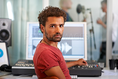 Buy stock photo A handsome young sound engineer sitting in front of his mixing desk