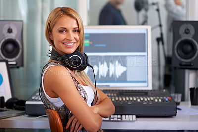 Buy stock photo A lovely young audio engineer sitting in front of her mixing console with her arms folded