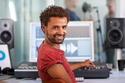 Buy stock photo A handsome young sound engineer sitting in front of his mixing desk - portrait