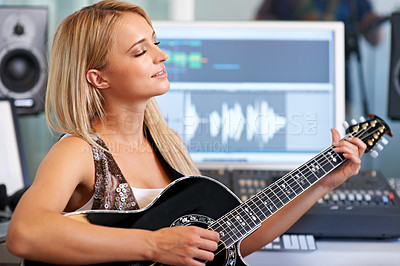 Buy stock photo A beautiful blonde woman playing guitar in a recording studio