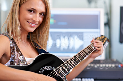 Buy stock photo A beautiful blonde guitarist sitting in a recording studio with her instrument - portrait