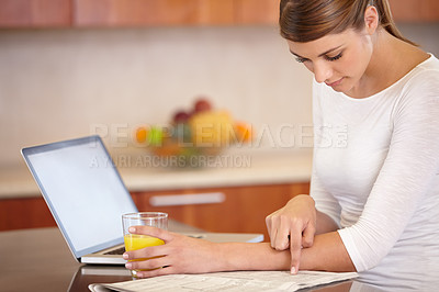 Buy stock photo A young woman reading the newspaper and enjoying a glass of orange juice in the morning