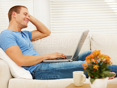 Buy stock photo An attractive young man working on laptop in the living room