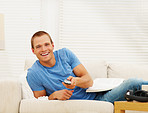 Young guy holding a television remote, relaxing at home