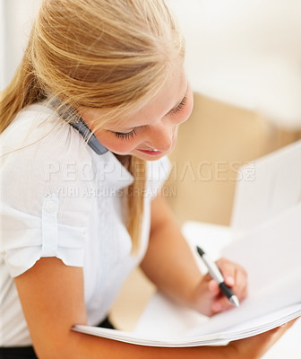 Buy stock photo Cute business female writing a note during a conversation on the mobile