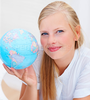 Buy stock photo Closeup portrait of a charming young female smiling while holding a world globe