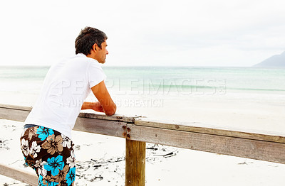 Buy stock photo Mature man relaxing on a wooden railing looking at the open sea