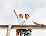 Happy father and son standing on a wooden railing outdoors, son pointing away