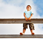 Cute little boy standing on a railing over a clouded sky