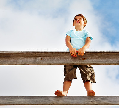 Buy stock photo Upward view of an adorable small boy standing on a wooden railing against a clouded sky