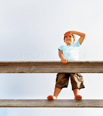 Buy stock photo Upward view of a cute small boy standing on a wooden railing searching something