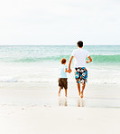 Rear view of a father and son running towards the sea water