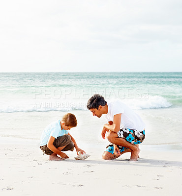 Buy stock photo Happy father and son on a beach vacation, boy playing with a conch shell
