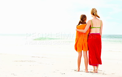 Buy stock photo Rear view of a mother and daughter standing isolated at the beach wrapped in a towel