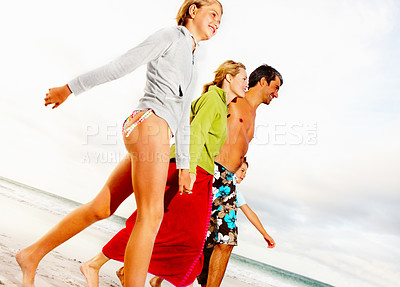 Buy stock photo Family taking a walk at the sea shore on their beach vacation