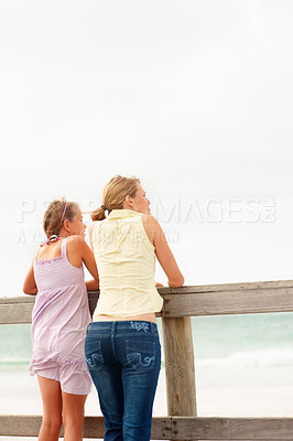 Buy stock photo Rear view of a mother and daughter standing by a wooden railing at the sea shore