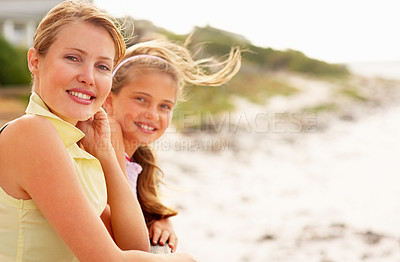 Buy stock photo Pretty mature woman at the beach with her teenage daughter at the back