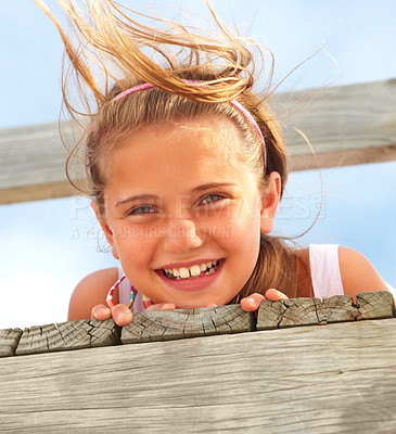 Buy stock photo Upward closeup portrait of a happy young girl lying on a wooden bridge outdoors