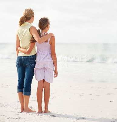 Buy stock photo Rear view of a mother and teenaged daughter standing together on the beach