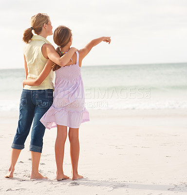 Buy stock photo Rear view of a mother and teenaged daughter standing on the beach, girl pointing towards the sea