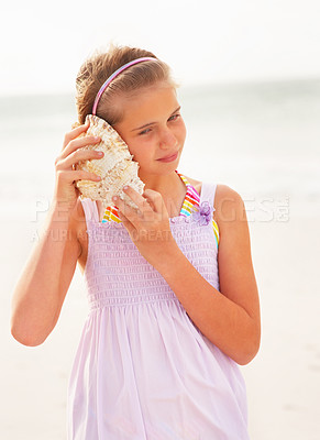 Buy stock photo Cute teen girl hearing a conch shell at the sea shore