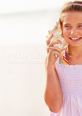 Buy stock photo Cropped image of a happy teenaged girl hearing a conch shell isolated at the beach