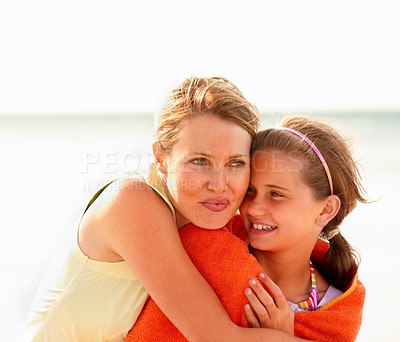 Buy stock photo Happy teen girl being embraced by mother while on their beach vacation