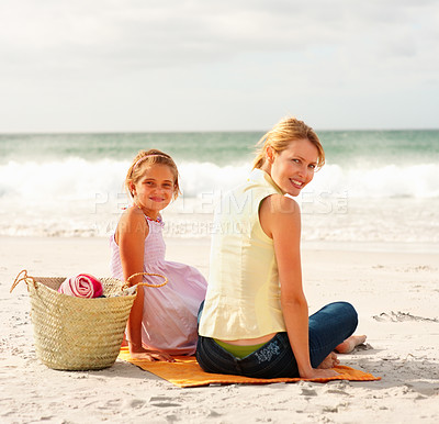 Buy stock photo Happy mother and daughter sitting together at the sea shore with a picnic basket