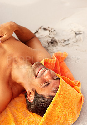 Buy stock photo Happy mature man lying on the sand with the towel partially covering his head
