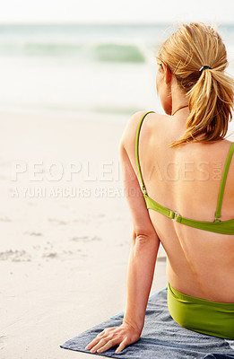 Buy stock photo Rear view of a young woman in green bikini sitting relaxed at the sea shore
