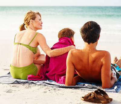 Buy stock photo Rear view of a father, mother and son sitting on the sea shore