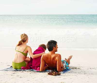 Buy stock photo Father, mother and son sitting on the sea shore facing the ocean