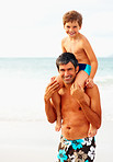 Father carrying his son on the shoulders while on the beach
