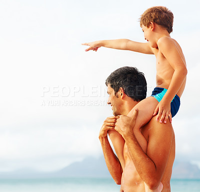 Buy stock photo Happy son having a ride on his father's shoulders while pointing away at the beach
