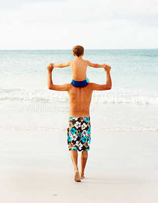 Buy stock photo Rear view of a man carrying his son on his shoulders walking towards the sea