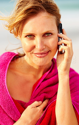Buy stock photo Beach vacation - Portrait of a young woman wrapped in a pink towel speaking on the cellphone