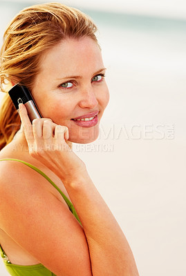 Buy stock photo Portrait of a lovely young female speaking on the cellphone while at the beach