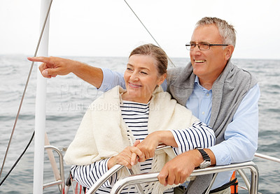 Buy stock photo Happy old couple embracing each other on sailboat, man pointing away